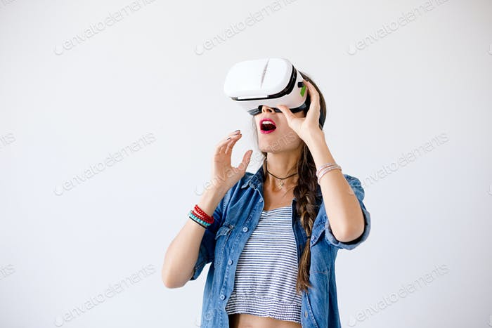 Excited girl with VR glasses in studio