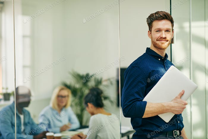 Smiling young businessman standing with his laptop in an office
