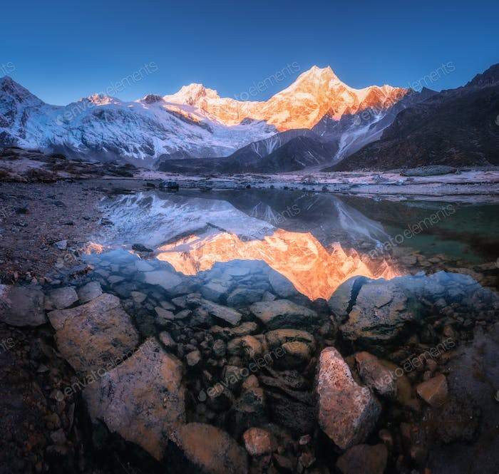 Snowy mountain with illuminated peaks is reflected in lake