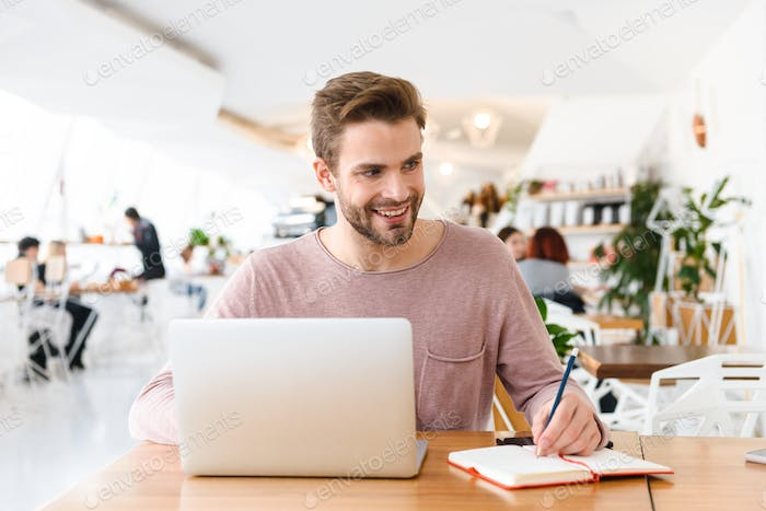 Image of young man working on laptop while sitting in cafe indoors
