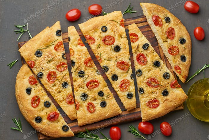 Focaccia, pizza, italian flat bread with tomatoes, olives and rosemary on dark brown table