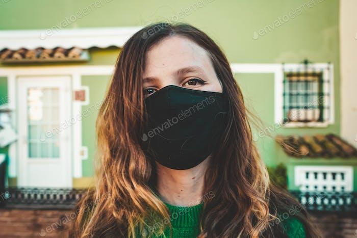 Bild einer Frau in grün mit einer schwarzen Gesichtsmaske