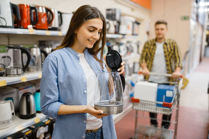 Couple looking electric kettle, electronics store