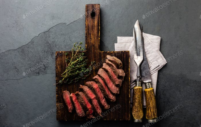 Slices of medium rare beef steak on wooden board, vintage carving cutlery, slate background