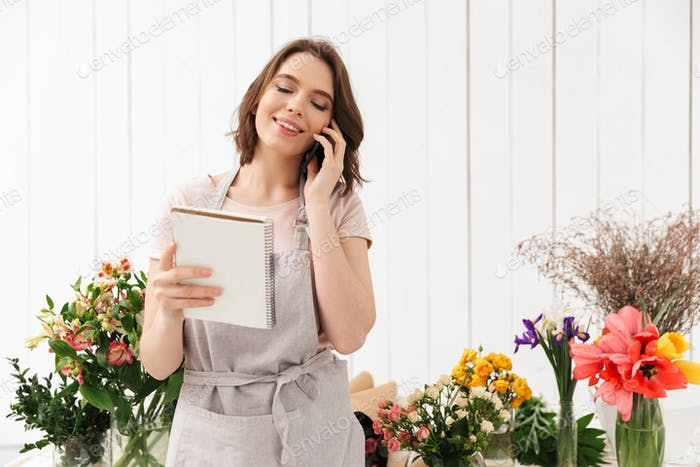 Young florist woman standing near table with different flowers i