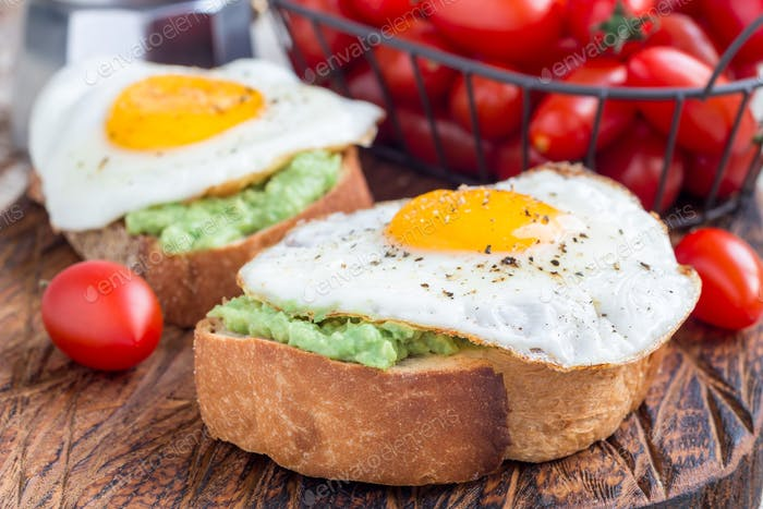 Open sandwiches with mashed avocado and fried egg, horizontal