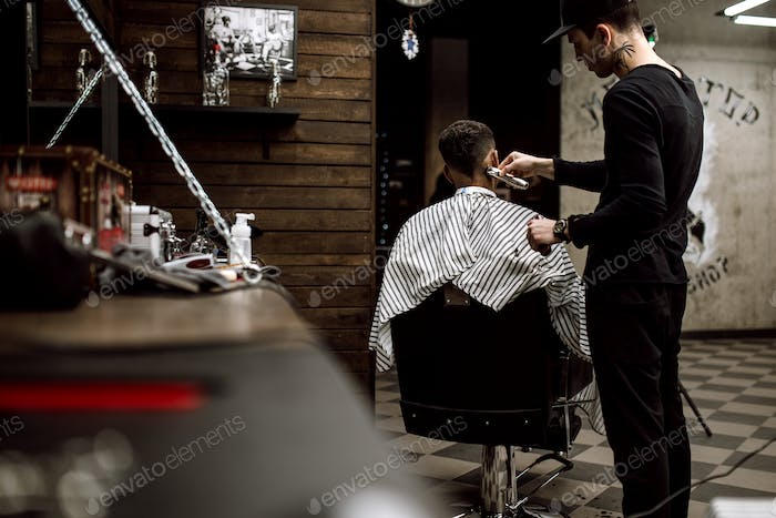 The fashion barber dressed in black clothes makes a razor cut hair for a stylish black-haired man in