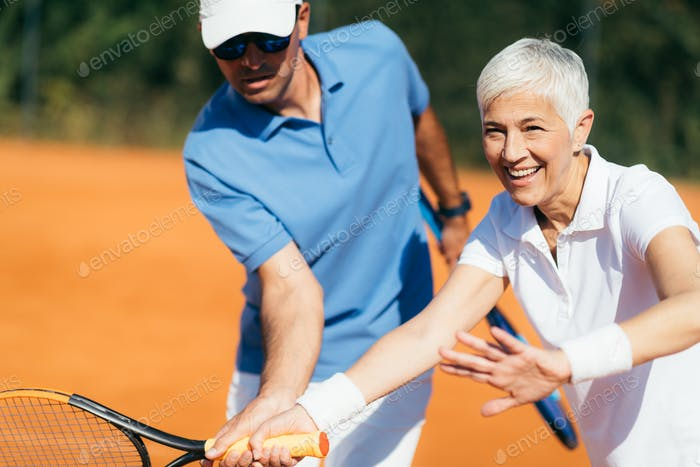 Aktive Senior Frau üben Tennis