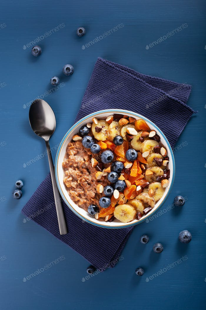 chocolate oatmeal porridge with blueberry, nuts, banana, dried a