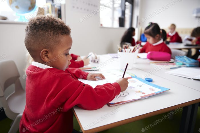 Junge schwarze Schuljunge tragen Schuluniform sitzen an einem Schreibtisch in einer Säuglingsschule Klassenzimmer Zeichnung