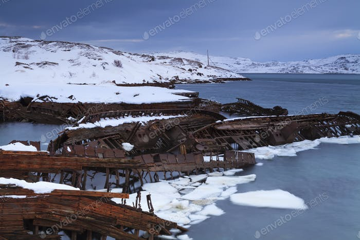 View of snow-covered shore with old boats