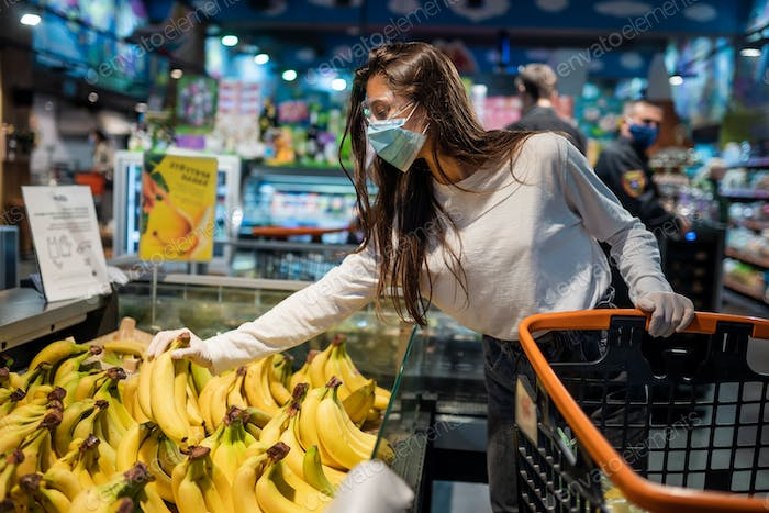 The girl with surgical mask is going to buy bananas