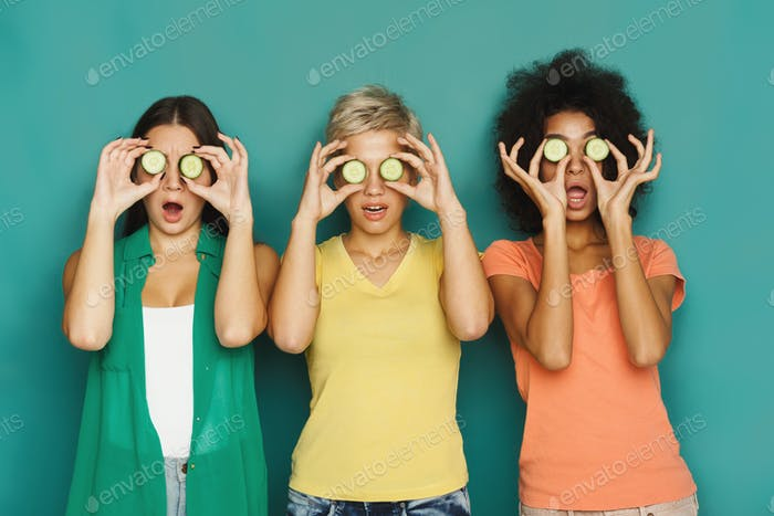 Three beautiful girls covering eyes with cucumber pieces