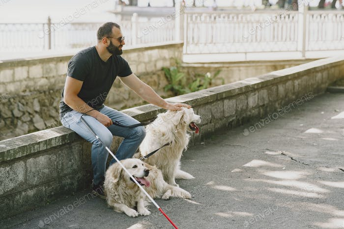 Blind man with guide dog in a summer city