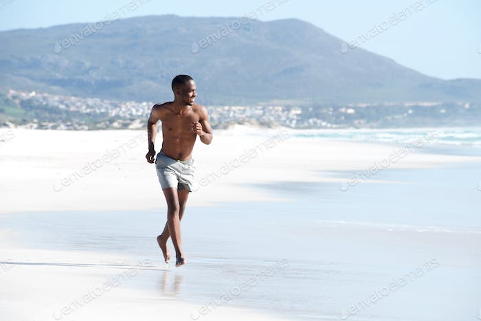 Young man running along the beach