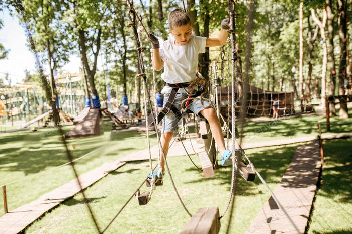 Little boy climbs in rope park at sunny day