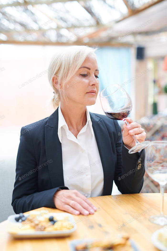 Professional female sommelier evaluating smell and taste of red wine