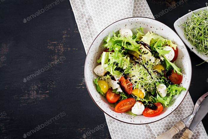 Vegetarian salad with cherry tomato, mozzarella and lettuce. Italian cuisine. Top view. Flat lay