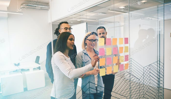 Smiling work colleagues brainstorming with notes on a glass wall