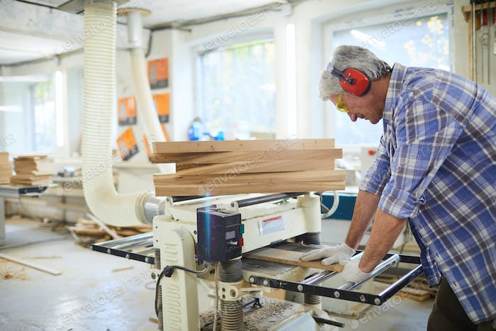 Concentrated carpenter working with wooden plank at machine
