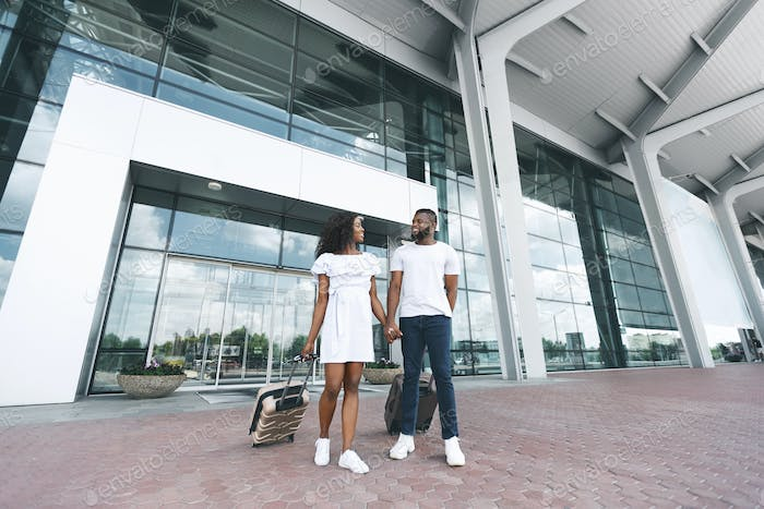 African american couple walking out of airport building with luggage