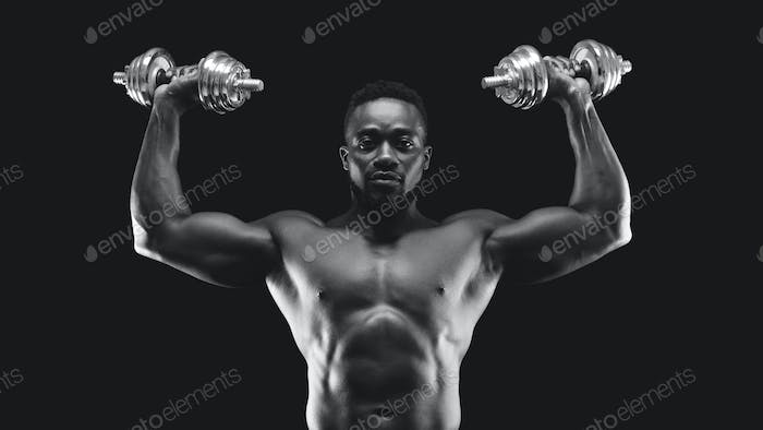 African american bodybuilder pushing barbells up, working out
