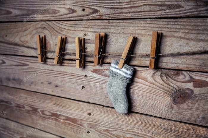 gray sock with a clothespin on a wooden background