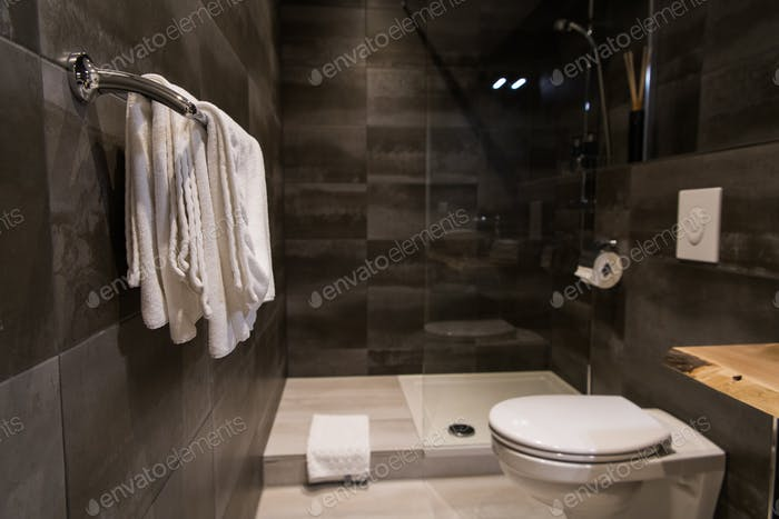 Clean white towels on a hanger at bathroom against grey wall tiles