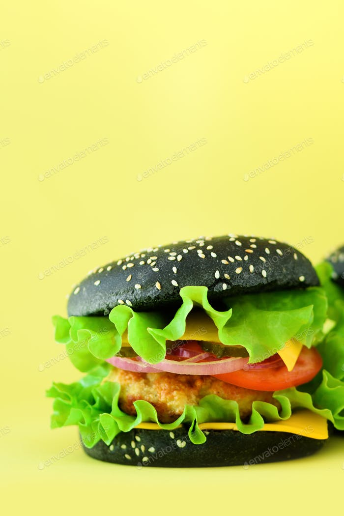 Fresh meat black burgers on yellow background. Take away meal. Fast food concept. Unhealthy diet