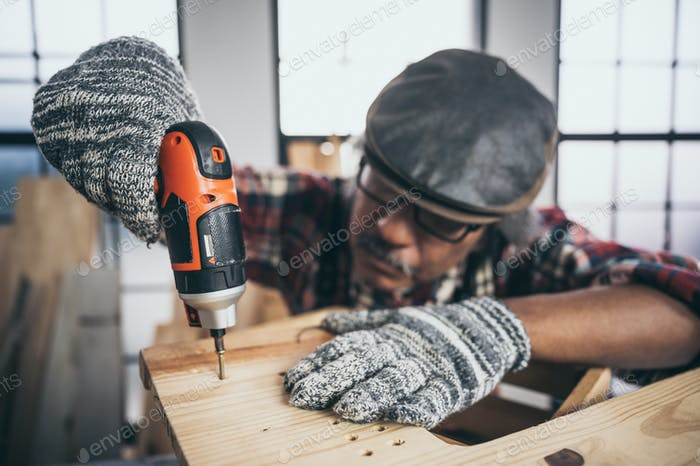Carpenter is using a drill bit to drill wood