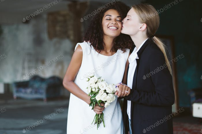 Young woman with blond hair in black suit kissing in cheek prett