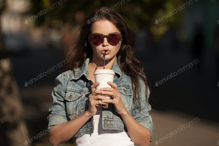 Young Smiling Woman Drinking Coffee To Go In A Park.