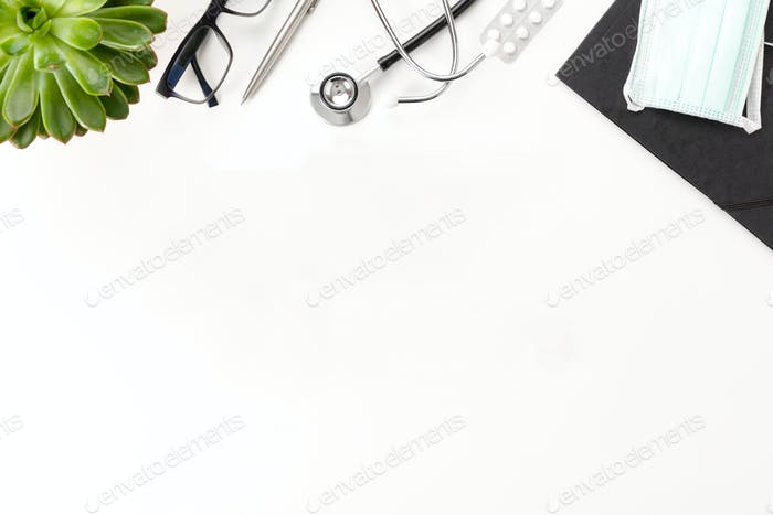 Doctors desk With Stethoscope And Eyeglasses By Plant On Table