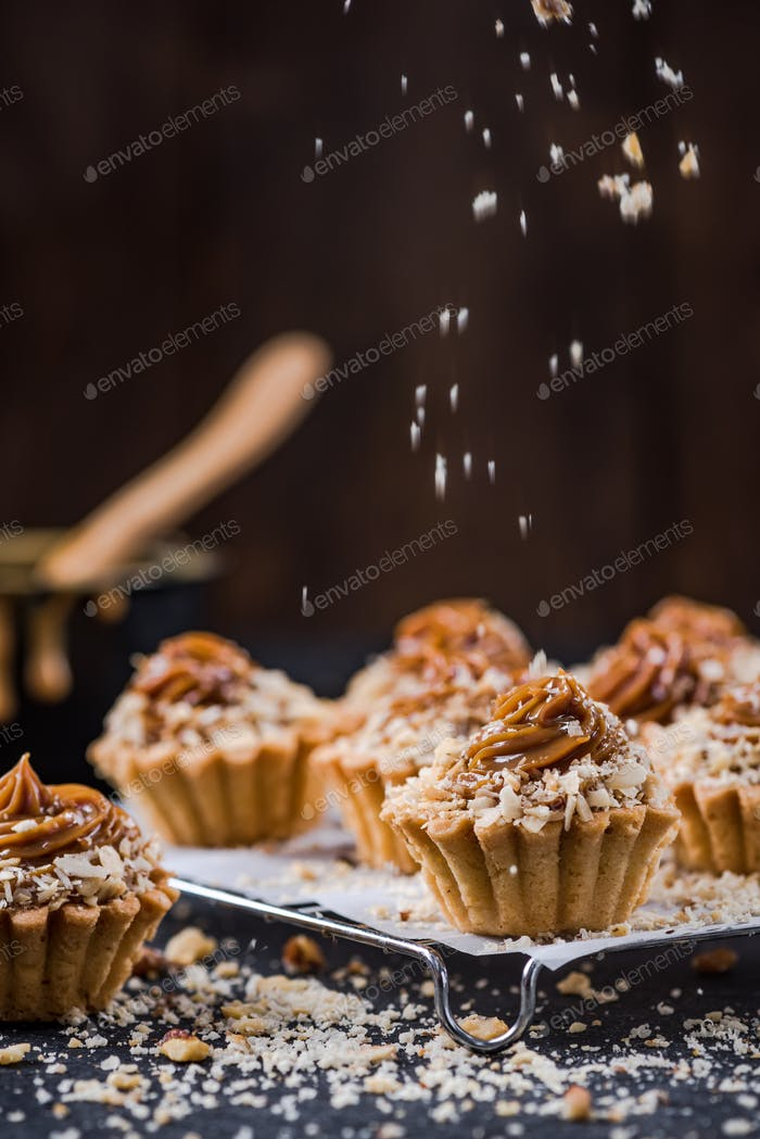 Topping salted caramel cupcakes with walnuts