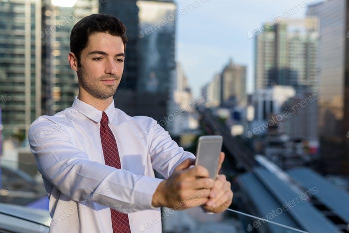 Portrait of young handsome businessman in city using phone