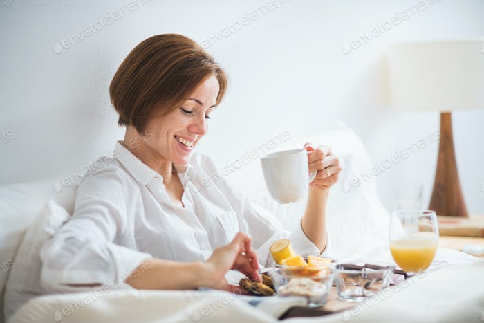 A woman having breakfast in bed in the morning.