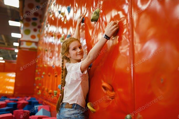 Little girl on climbing wall, entertainment center