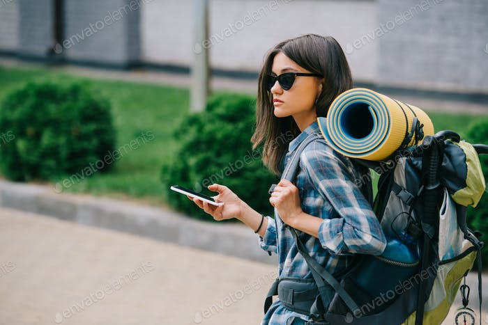 young female backpacker in sunglasses holding smartphone