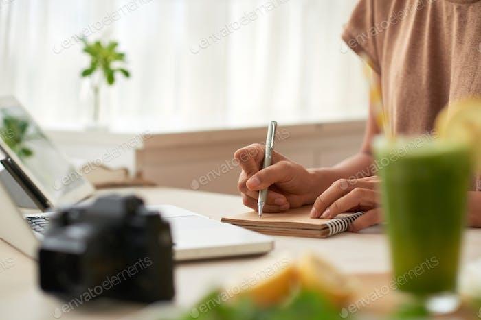 Blogger writing down ideas