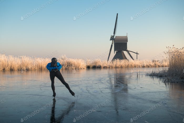 Ice skating past frosted reeds in the Netherlands