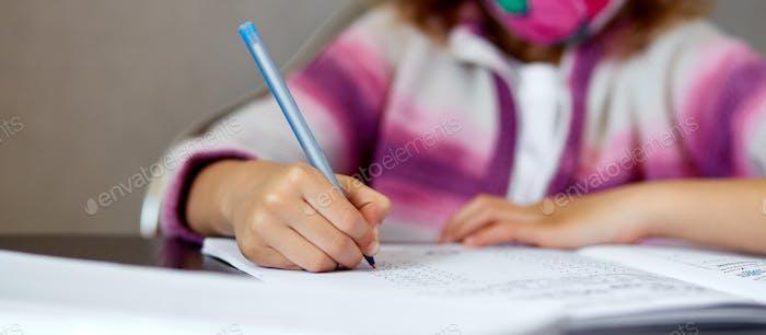 Unrecognizable girl doing homework, writing education concept, Coronavirus