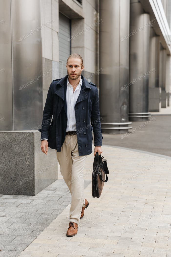 Image of handsome young confident businessman walking on city street