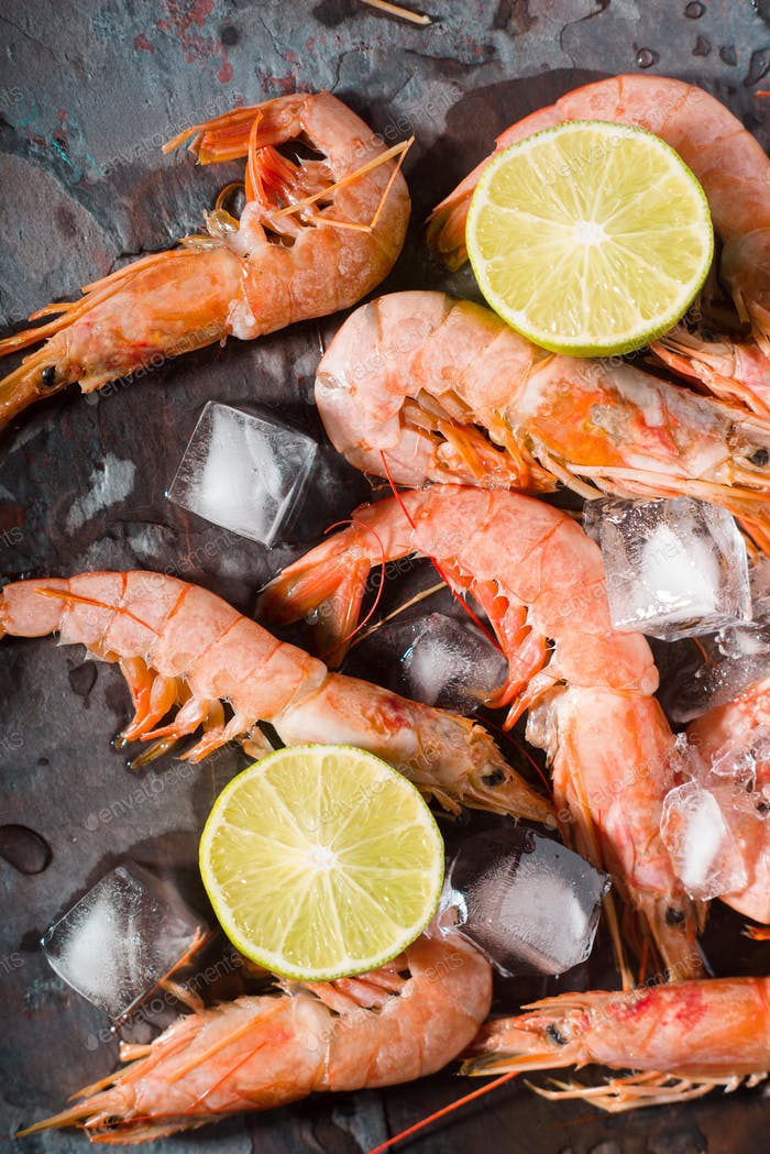Prawns with lemon and ice cube on the stone