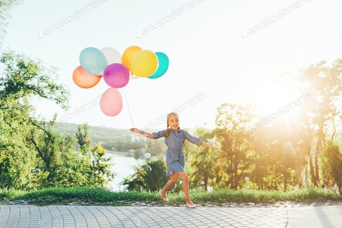 Cute girl holding colorful balloons in the city park, playing an