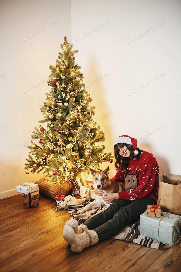 Happy girl in santa hat hugging with cute dog