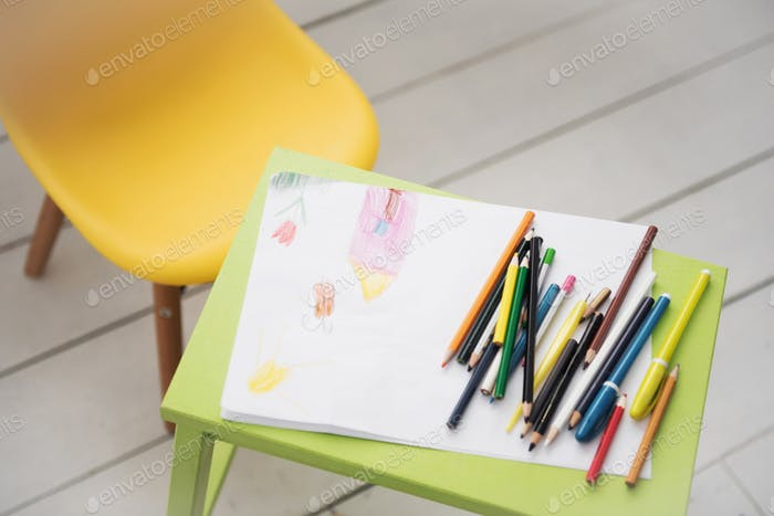 A frame with a kid drowing and colored pencils