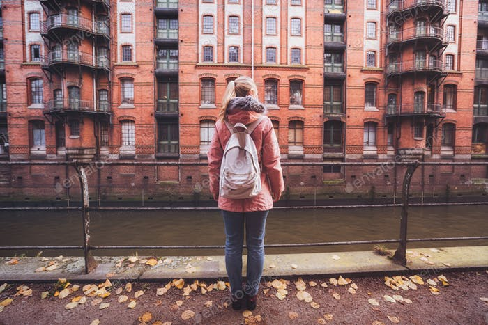Back rear view of adult woman tourist with white backpack against beautiful historic Speicherstadt
