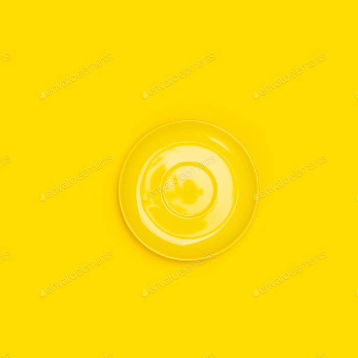 Top view of yellow ceramic plate (saucer) on yellow background
