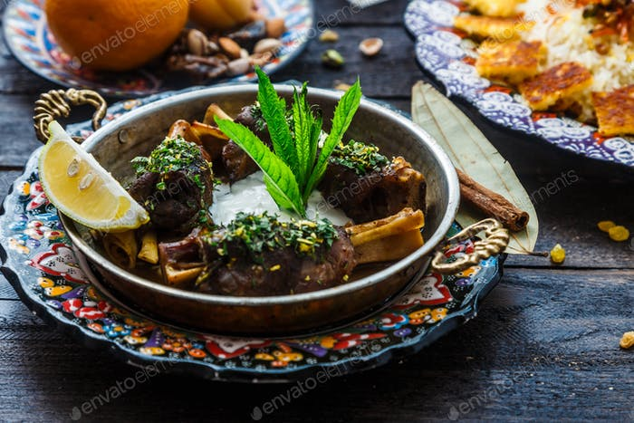 Baked lamb shanks middle eastern style in copper pan