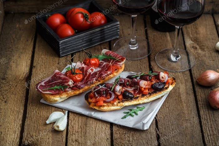 Wine appetizer set. Glass of red wine, brushettas with fresh tomato and jamon